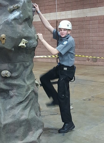 A police officer, wearing a helmet, attempting to climb a climbing wall